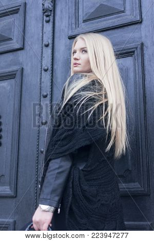 portrait of an attractive girl dressed in black with a long blue hair that stands in front of the black door retro look