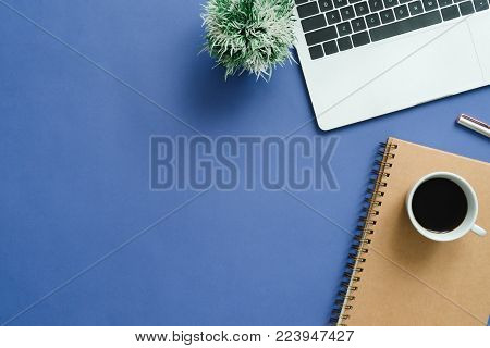 Minimal work space - Creative flat lay photo of workspace desk. Top view office desk with laptop, notebooks and coffee cup on blue color background. Top view with copy space, flat lay photography.