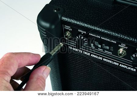 Connecting the cable from guitar to amplifier.