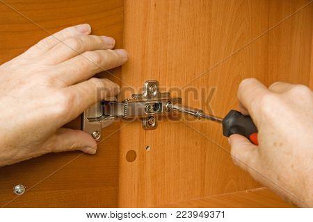 Carpenter adjusting a cabinet door hinge at a home.