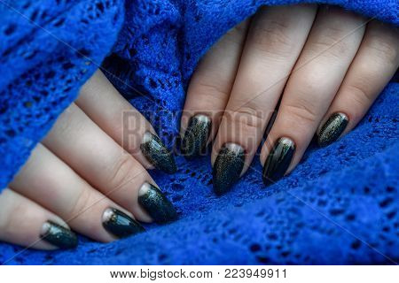 Beautiful winter manicure. Black lacquer with luster and white patterns of snow and frost. The blue background is also with beautiful curled drawings.