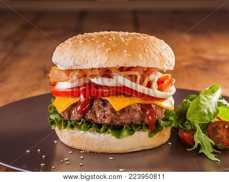A juicy charcoal broiled hamburger with bacon, onion rings, tomato, cheddar cheese and vegetables.