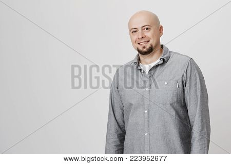 Portrait of good-looking bald man in casual clothes joyfully smiling during pleasant conversation, standing against gray studio background while talking with friends. Positive emotions and face expression