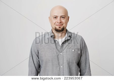Human face expressions and emotions. Thoughtful good-looking bald man in casual clothes, looking at camera and pleasantly smiling. Hairless positive male model posing indoors