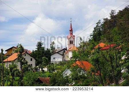 The white and red Postojna town in Slovenia hidden among green trees, on the main plan the bell tower and the church