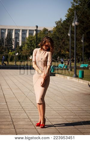 young beautiful woman in a dress poses outdoor on background of the city