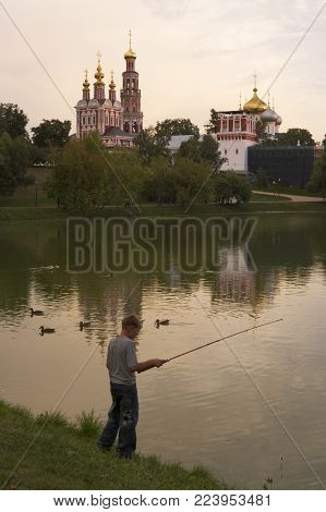 MOSCOW, RUSSIA: BOY FISHING IN POND BY NOVODEVICHY CONVENT AND ASSUMPTION CHURCH MOSCOW, SEPTEMBER 2005, MOSCOW, RUSSIA