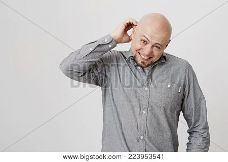 Headshot of clueless perplexed bald european man in grey shirt looking at camera with confused and puzzled expression, scratching back of his head, having forgot about his wife's birthday