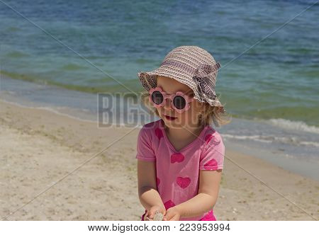 Little funny girl (4 years old) at sea in a big striped hat. Selective focus.