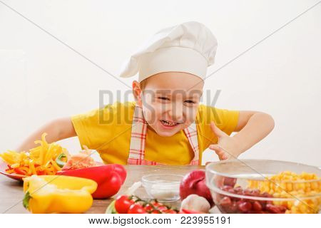 Healthy eating. Happy child in cook cap prepares and eats vegetables in kitchen