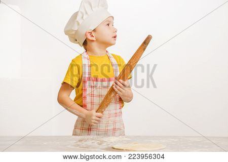 Details of children's hands kneading dough. Cheerful cook child boy in a cap prepares burritos or pizza