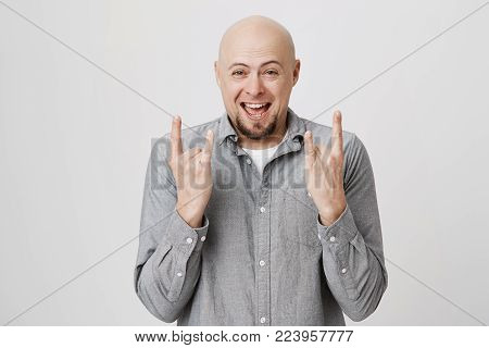 Emotional cheerful bald man with beard in gray shirt smiling at camera joyfully, rejoicing success, showing rock sign with both hands. Positive emotions, face expressions and body language