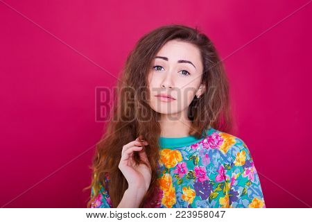 Anger and rage concept. Young expressive woman show her bad face. Angry nervous annoyed girl portrait on red background.