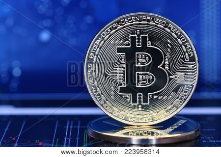 Bitcoin. Crypto currency Bitcoin, BTC, Bit Coin. Macro shot of Bitcoin coins on blue background and chart under coins. Blockchain technology, bitcoin mining concept
