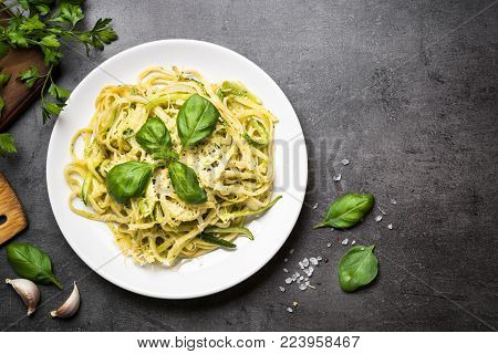 Pasta spaghetti with zucchini, basil, cream and cheese on black stone table. Vegetarian vegetable pasta. Zucchini noodles. Top view copy space.
