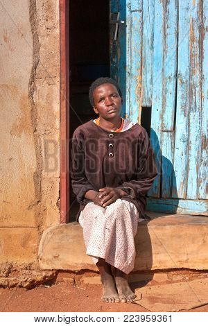 African woman in front of the house in the village, Botswana