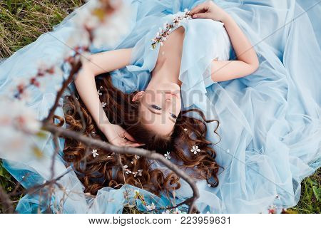 Spring touch. Happy beautiful young smiling woman in blue dress enjoy fresh flowers and sun light in blossom park at sunset