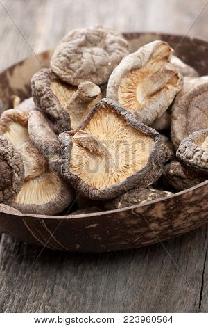 dried shiitake mushrooms in a bowl on the old wooden background close-up