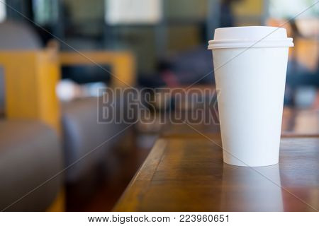 Single hot latte Single hot latte in paper cup on wood table
