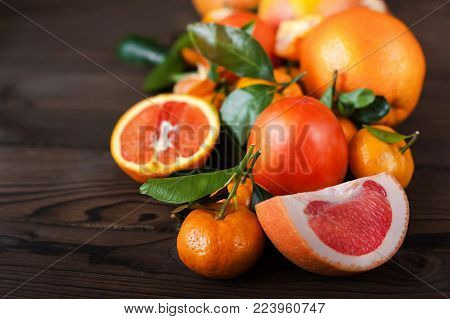 A lot of juicy ripe fruits on a dark wooden background. Persimmon, Mandarins with branches and leaves, grapefruit, oranges. Background and space for your text.