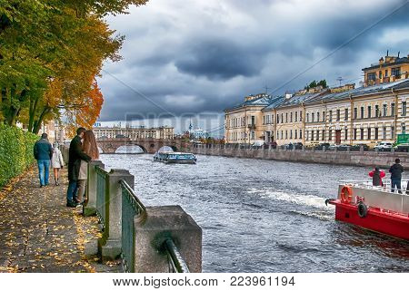 SAINT - PETERSBURG, RUSSIA - OCTOBER 15, 2017: People inside the Summer Garden near Fontanka River. On the background is Pracheshny Bridge and The Neva River
