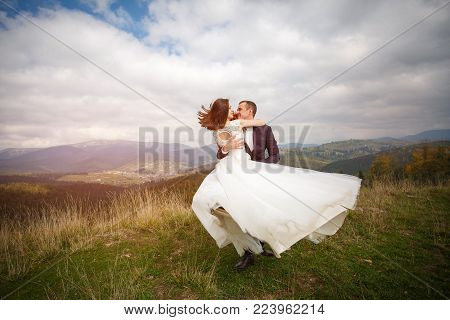 Loving couple are newlyweds in the mountains. Stylish bride with a bouquet kisses the groom. love, fidelity and shadowing concept. Mountain Walk and Hiking.