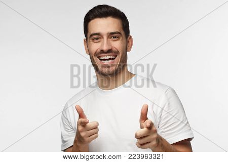Hey you! Young man pointing to camera with fingers isolated on gray background