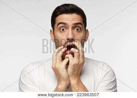 Astonished bug-eyed man covering his mouth with both hands, looking shocked. Surprised, embarrassed and confused young male showing omg emotion