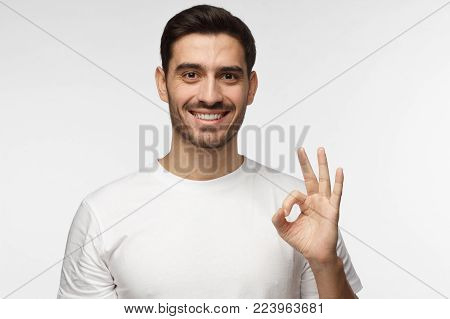 Young man in white tshirt having happy look, smiling, gesturing, showing OK sign. Caucasian male showing OK-gesture with his fingers. Body language concept