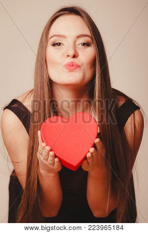 Love help and charity concept. Young beauty cute long haired woman girl in black dress blowing kiss holding heart box gift present in studio.