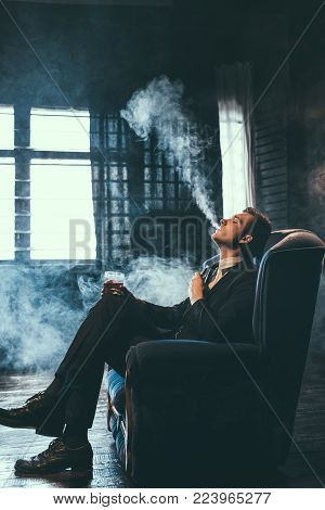 Man gets pleasure from vaping. Healthy alternative to nicotine cigarettes. Exhaling lots of fumes and feeling relaxed and satisfied.