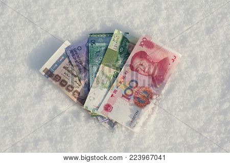 A bundle of Chinese money in the snow. Banknotes of one hundreds, twenty and ten RMB. Concept