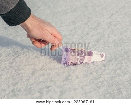 A man's hand is getting money of south-east Asia from the snow in winter. Currency of Indonesia