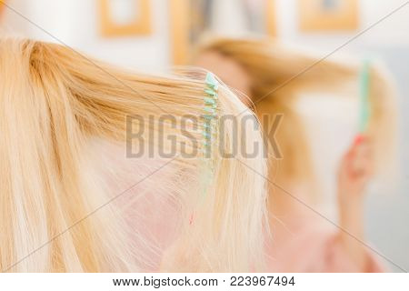 Woman wearing dressing gown brushing her long blonde hair, morning beauty routine. Haircare and hairstyling concept.