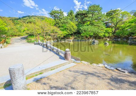 Stone bridge and pond in Maruyama Park, spring season, Higashiyama District in Kyoto, Japan. Maruyama Park is Kyoto's most famous cherry-blossom viewing hanami spot.