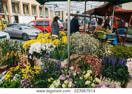 Prague, September 25, 2017:A small business for selling flowers. The seller does the work in the background. Street shop. There are different kinds of flowers on the counter