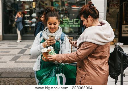 Prague, September 25, 2017: Two friends after shopping in the store stand on the street and take pictures of a traditional Czech dessert called Tridlo and make a post in social networks