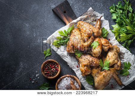Baked chicken wings. Wings of barbecue on dark stone table. Top view copy space.