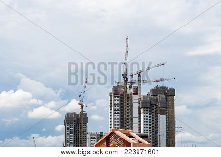 High rise tower crane and new unfinished residential townhouse under construction, buildings front view. Urban development theme. Blue sky and cloud background