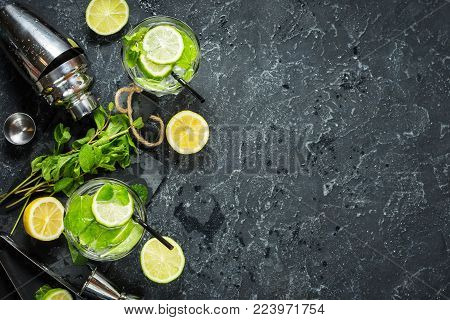 Mojito cocktail with lime and mint in highball glass on a stone table. Drink making tools and ingredients for cocktail. Copy space and top view