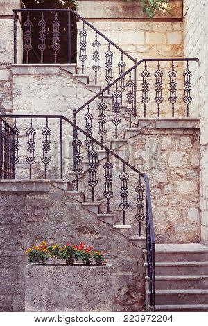 Ancient stone staircase with ornate wrought handrail
