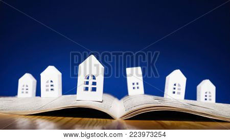 Open newspaper with paper houses on blue background. Concept of rent, search, purchase real estate.