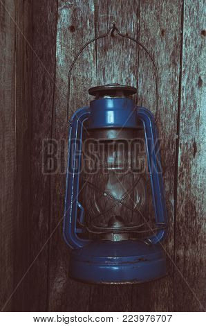 Extinguished the kerosene lamp hangs on old wooden wall in the morning