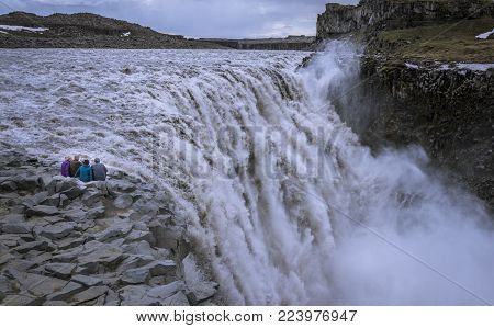 Senior travelers sitting on the edge, contemplating Detifoss waterfall. Retirees traveling arround the world.