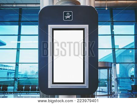 Blank electronic departures and arrival informational billboard with clean space for publicity content or text message, vertical LCD board with screen mock-up in interior of modern airport terminal