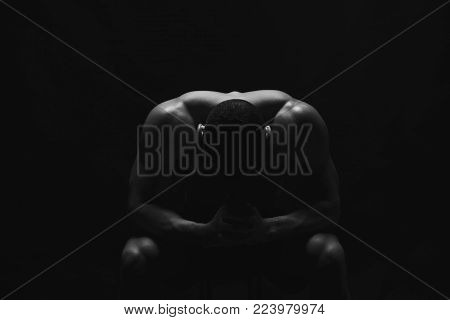 Pensive strong man sitting with head down. Male fitness model with naked torso showing strong neck and biceps muscles. Studio shot on black background, low kye, copy space, black and white image