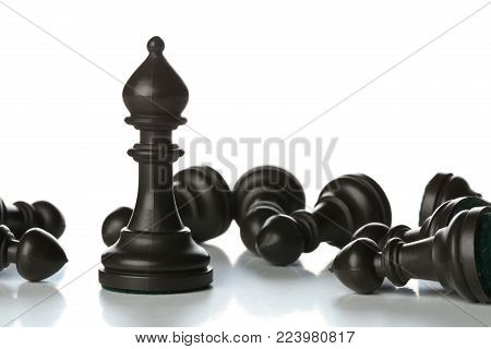 Runner chess figure standing in between fallen over pawn chess figures - management, leadership, teamlead or strategy concept over white background