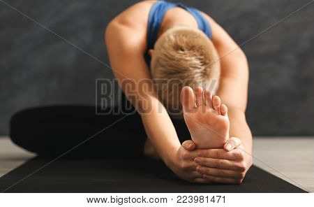 Unrecognizable fitness woman warmup stretching, training at grey background indoors. Young slim girl making yoga exercise, closeup of foot, copy space