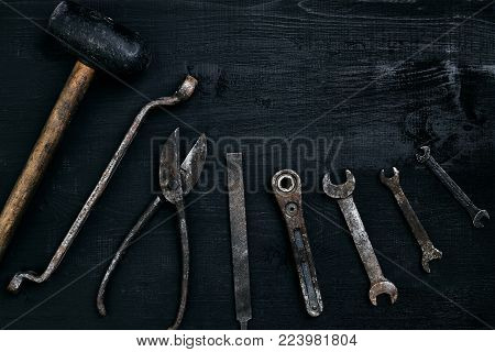 Old, rusty tools lying on a black wooden table. Hammer, chisel, metal scissors, wrench. Top view. Copy space. Still life. Flat lay