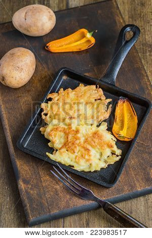 Potato pancakes (potato fritters) on a black cast-iron frying pan, next to a pod of yellow sweet pepper and raw potatoes on an old wooden table. Vegetarian food. Selective focus.